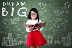 Niño con el texto grande ideal en clase Imagenes de archivo