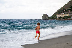 Niño con el traje de baño anaranjado que corre en la playa Imagen de archivo