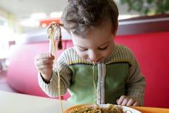 Niño con espaguetis Imagenes de archivo