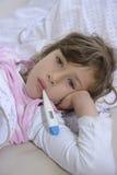Niño con fiebre en cama fotografía de archivo