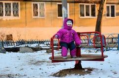niño con gusto vestido que se sienta en un oscilación en el frío del invierno Imagen de archivo