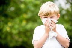 Niño con la alergia que limpia su nariz imagen de archivo libre de regalías