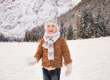 Niño con la bola de nieve que se coloca entre las montañas coronadas de nieve Foto de archivo libre de regalías
