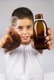 Niño con la botella del jarabe imagenes de archivo