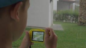 Niño con la cámara que hace las fotos durante día lluvioso