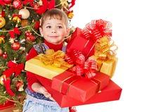 Niño con la caja de regalo cerca del árbol de navidad. Fotos de archivo