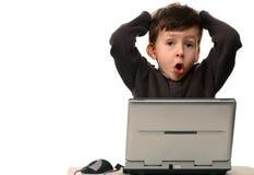 Niño con la cara dada una sacudida eléctrica que se sienta delante de la computadora portátil Imágenes de archivo libres de regalías
