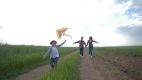 Ni?o con la cometa en funcionamientos de las manos cerca de padres jovenes en campo en la c?mara lenta en fondo del cielo soleado metrajes