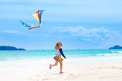 Niño con la cometa Juego de los niños Vacaciones de la playa de la familia Foto de archivo libre de regalías