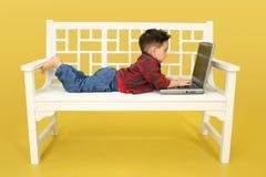 Niño con la computadora portátil Imagenes de archivo