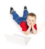 Niño con la computadora portátil Foto de archivo