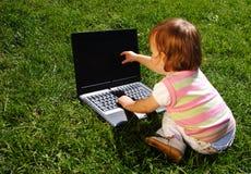 Niño con la computadora portátil Fotos de archivo libres de regalías