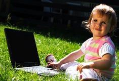 Niño con la computadora portátil Fotografía de archivo libre de regalías