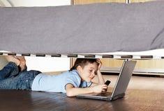 Niño con la computadora portátil y el teléfono bajo la cama Fotos de archivo