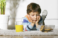Niño con la diabetes que mira las galletas. Imágenes de archivo libres de regalías