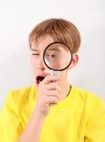 Niño con la lente que magnifica Foto de archivo libre de regalías