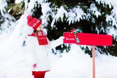Niño con la letra a Papá Noel en el buzón de la Navidad en nieve Imagen de archivo libre de regalías