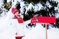 Niño con la letra a Papá Noel en el buzón de la Navidad en nieve Fotos de archivo libres de regalías
