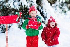 Niño con la letra a Papá Noel en el buzón de la Navidad en nieve Fotografía de archivo libre de regalías