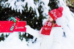 Niño con la letra a Papá Noel en el buzón de la Navidad en nieve Foto de archivo libre de regalías