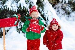 Niño con la letra a Papá Noel en el buzón de la Navidad en nieve Imágenes de archivo libres de regalías