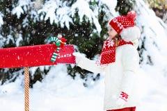 Niño con la letra a Papá Noel en el buzón de la Navidad en nieve Foto de archivo