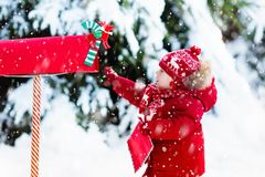 Niño con la letra a Papá Noel en el buzón de la Navidad en nieve Fotografía de archivo