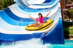 Niño con la madre en diapositiva de agua en el aquapark Fotografía de archivo