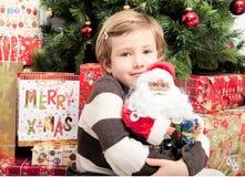 Niño con la muñeca de santa delante del árbol de navidad foto de archivo