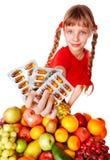 Niño con la píldora de la fruta y de la vitamina. Foto de archivo