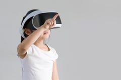 Niño con la realidad virtual, VR, tiro del estudio de las auriculares aislado en el fondo blanco Niño que explora el mundo virtua imagen de archivo