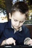 Niño con la tableta al aire libre en un parque Imágenes de archivo libres de regalías