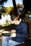 Niño con la tableta al aire libre en un parque Imagen de archivo libre de regalías