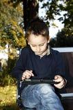 Niño con la tableta al aire libre en un parque Foto de archivo libre de regalías