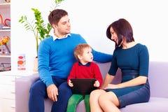 Niño con la tableta digital que habla con los padres Imagenes de archivo