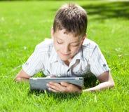 Niño con la tableta en el verano Foto de archivo