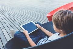 Niño con la tableta que se sienta al aire libre Foto de archivo libre de regalías