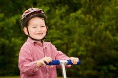 Niño con la vespa del montar a caballo del casco de seguridad Imagen de archivo