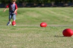 Niño con las bolas de rugbi rojas Imagenes de archivo