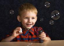 Niño con las burbujas de jabón foto de archivo