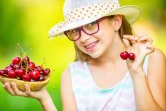 Niño con las cerezas Niña con las cerezas frescas Apoyos y vidrios de los dientes de la muchacha que llevan rubia caucásica linda Foto de archivo