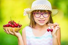 Niño con las cerezas Niña con las cerezas frescas Apoyos y vidrios de los dientes de la muchacha que llevan rubia caucásica linda Fotos de archivo