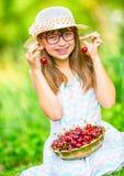 Niño con las cerezas Niña con las cerezas frescas Apoyos y vidrios de los dientes de la muchacha que llevan rubia caucásica linda Fotografía de archivo