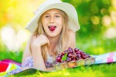 Niño con las cerezas Niña con las cerezas frescas Retrato de una chica joven sonriente con el cuenco lleno de cerezas frescas Imágenes de archivo libres de regalías