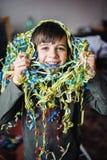 Niño con las flámulas alrededor del cuello y de la cabeza Foto de archivo libre de regalías