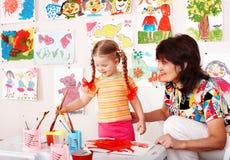 Niño con las pinturas del drenaje del profesor en sala de juegos. fotografía de archivo