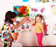 Niño con las pinturas del drenaje del profesor en sala de juegos. foto de archivo