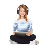 Niño con los auriculares y PC de la tableta Fotografía de archivo