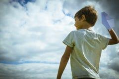 Niño con los aviones de papel contra el cielo azul Foto de archivo libre de regalías
