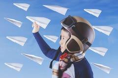 Niño con los aviones y el casco de papel Fotografía de archivo